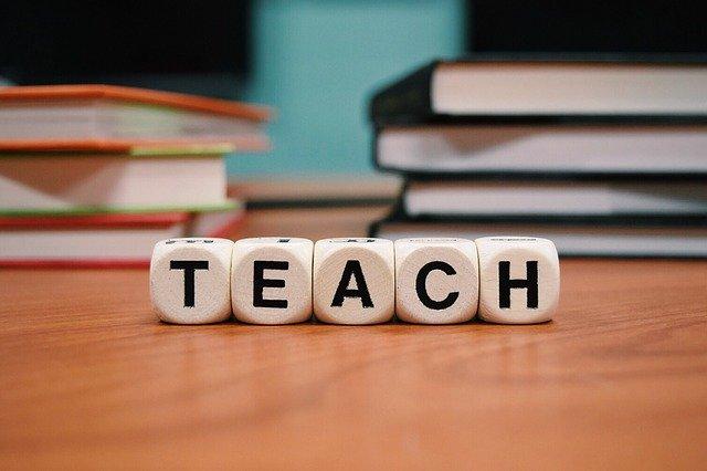 """nápis """"uč"""" nebo """"učit"""" poskládaný z kostek před knihami na stole"""
